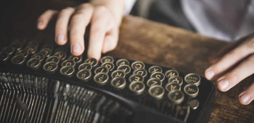 Close up of a hands writing on a vintage typewriter.